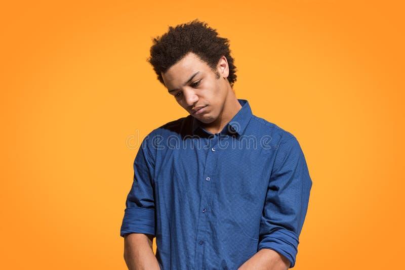 Bello annoiato annoiato dell'uomo isolato su fondo arancio immagine stock libera da diritti
