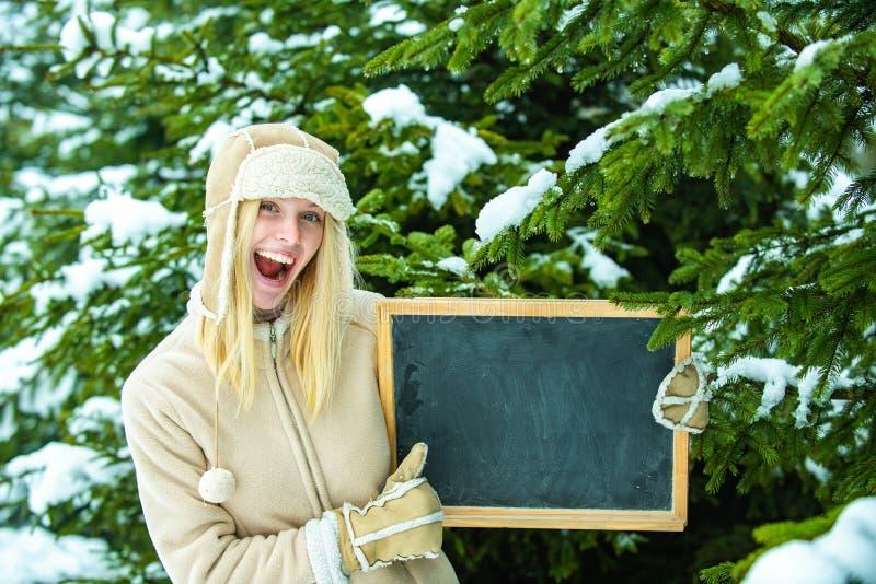 Bello annuncio per l'inverno Una ragazza col cappello caldo e i guanti tiene in mano una bacheca Salta il pollice da giovane fotografia stock libera da diritti