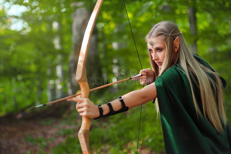 Bello arcere femminile dell'elfo nella caccia della foresta con un arco immagini stock