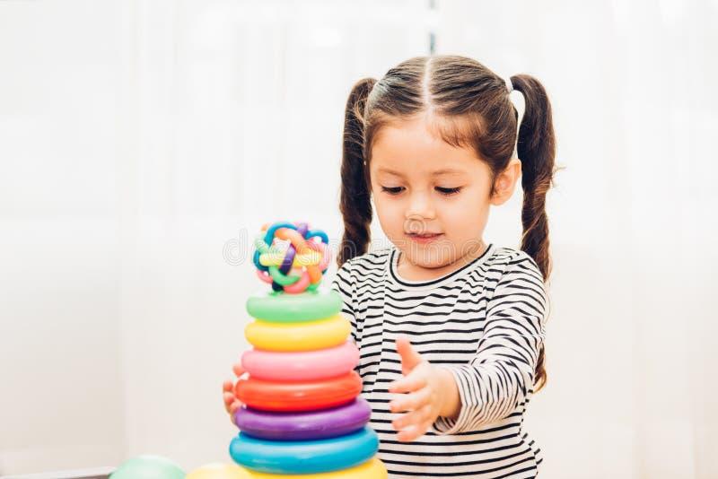 Bello asilo della neonata che gioca istruzione del giocattolo del ciclo fotografia stock libera da diritti