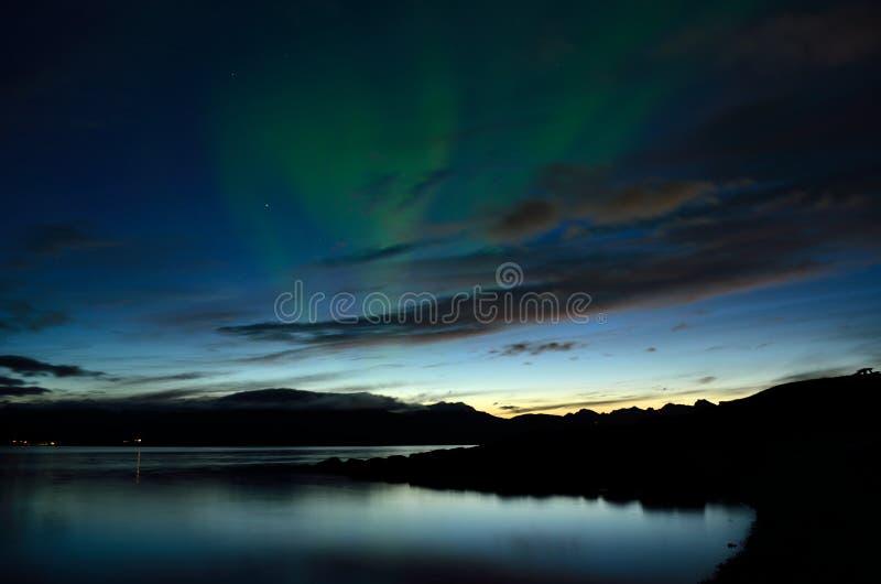 Bello aurora borealis che balla sopra il fiordo e le montagne calmi fotografia stock libera da diritti