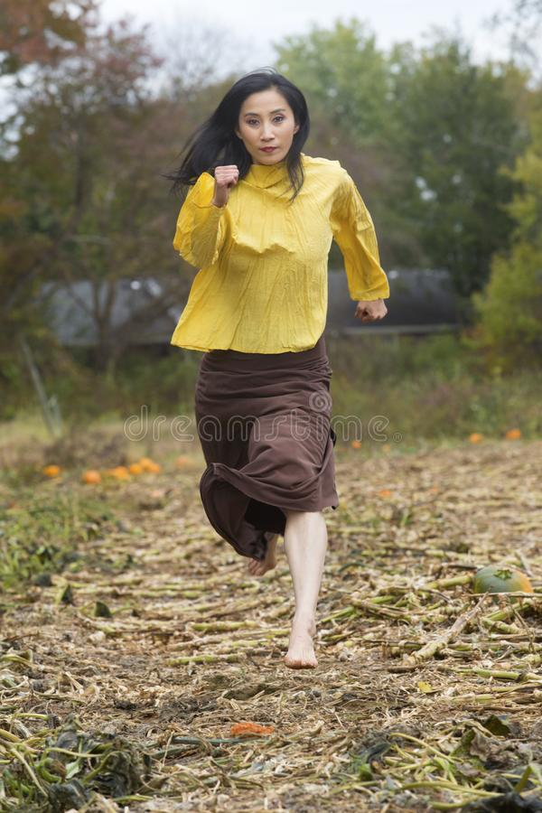 Bello ballerino della donna adulta che corre in una toppa della zucca di Connecticut immagini stock libere da diritti