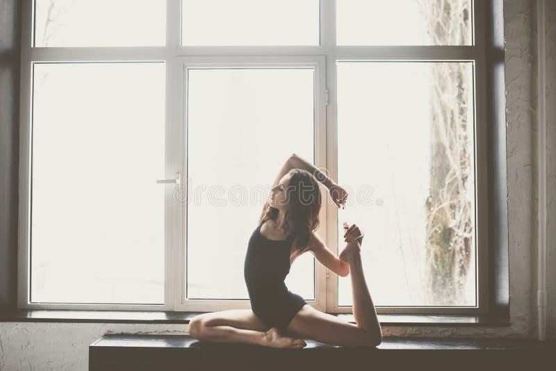 Bello ballerino della ragazza con capelli scorrenti lunghi in vestiti neri, costume da bagno, in una bella bella posa sulla grand fotografia stock libera da diritti