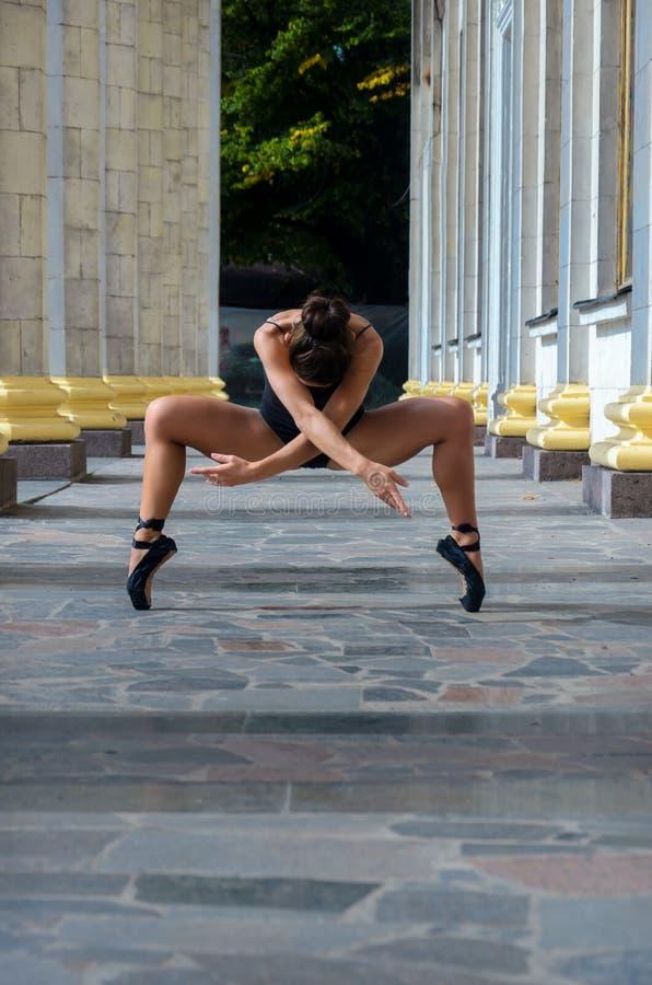 Bello ballerino snello della donna di sport in un vestito e in un pointe neri fotografia stock