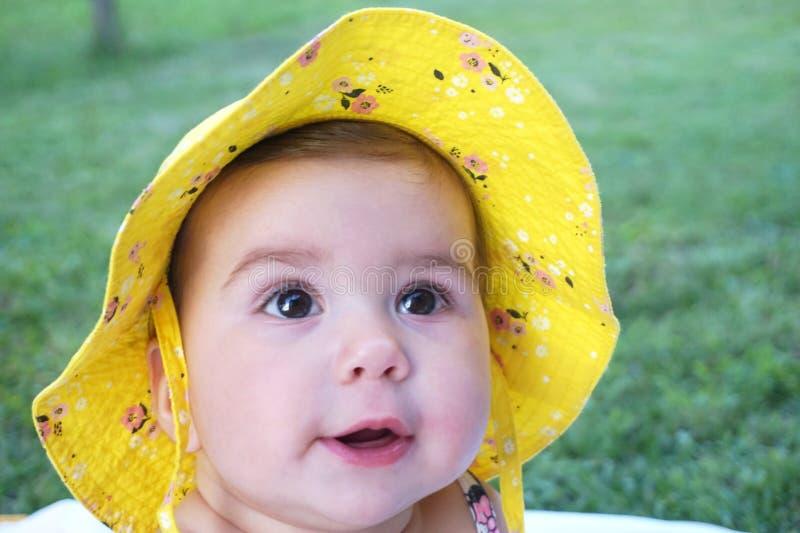 Bello, bambino adorabile e sveglio con il cappello giallo che esamina la distanza fotografia stock