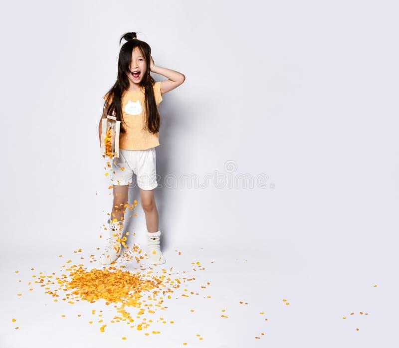 Bello bambino asiatico della ragazza alla prima colazione di mattina che versa fuori i fiocchi di mais che sbadigliano su grigio immagine stock