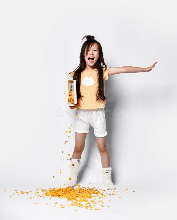 Bello bambino asiatico della ragazza alla prima colazione di mattina che versa fuori i fiocchi di mais che sbadigliano su grigio immagini stock