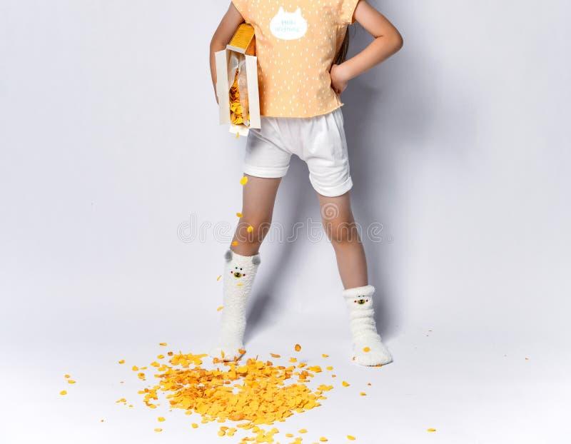 Bello bambino asiatico della ragazza alla prima colazione di mattina che versa fuori i fiocchi di mais che sbadigliano su grigio fotografia stock libera da diritti