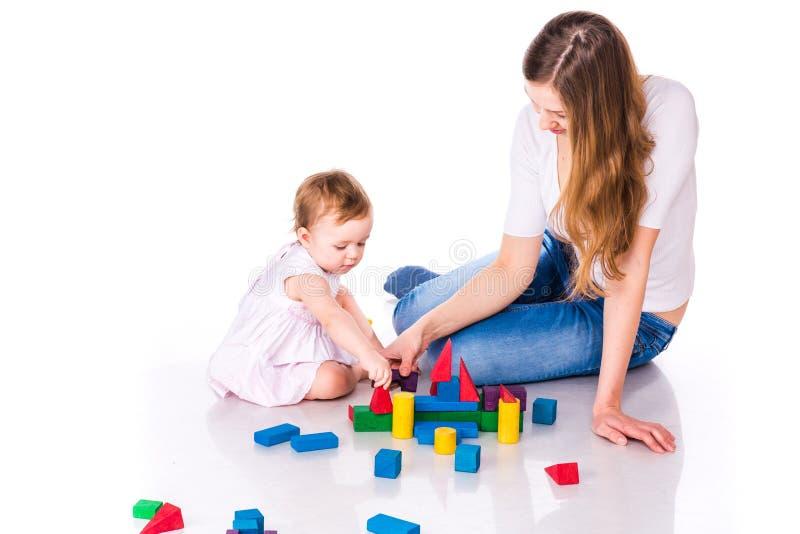 Bello bambino con la costruzione della madre con i cubi immagine stock