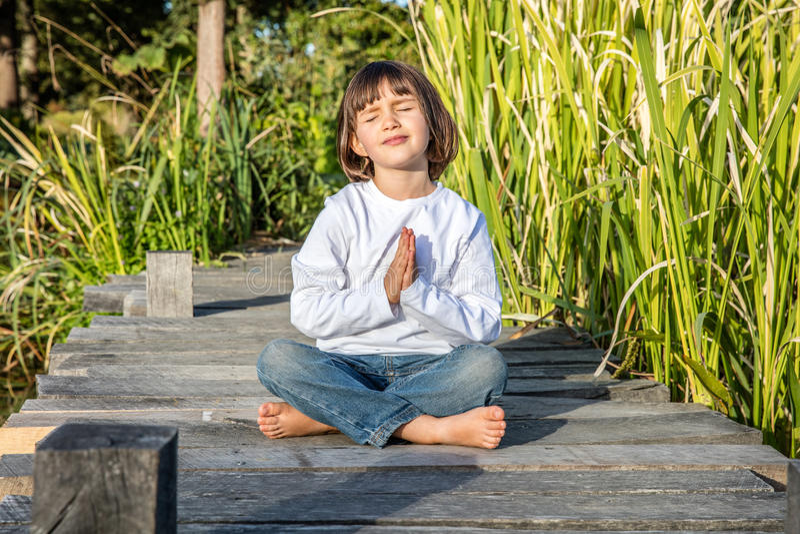 Bello bambino felice che fa i piedi nudi di yoga che si siedono sul legno immagine stock
