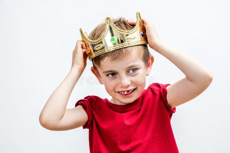 Bello bambino felice con un dente contorto che indossa una corona immagine stock libera da diritti