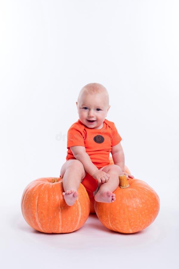 Bello bambino in maglietta arancio su un fondo bianco che si siede o fotografie stock
