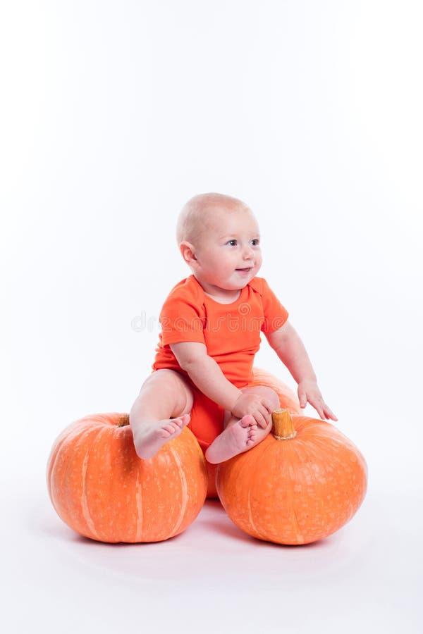 Bello bambino in maglietta arancio su un fondo bianco che si siede o immagini stock libere da diritti