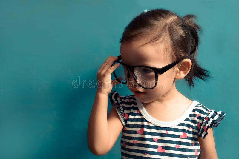 Bello bambino serio, ragazza con occhiali in mano, sfondo azzurro isolato con spazio fotografico immagini stock
