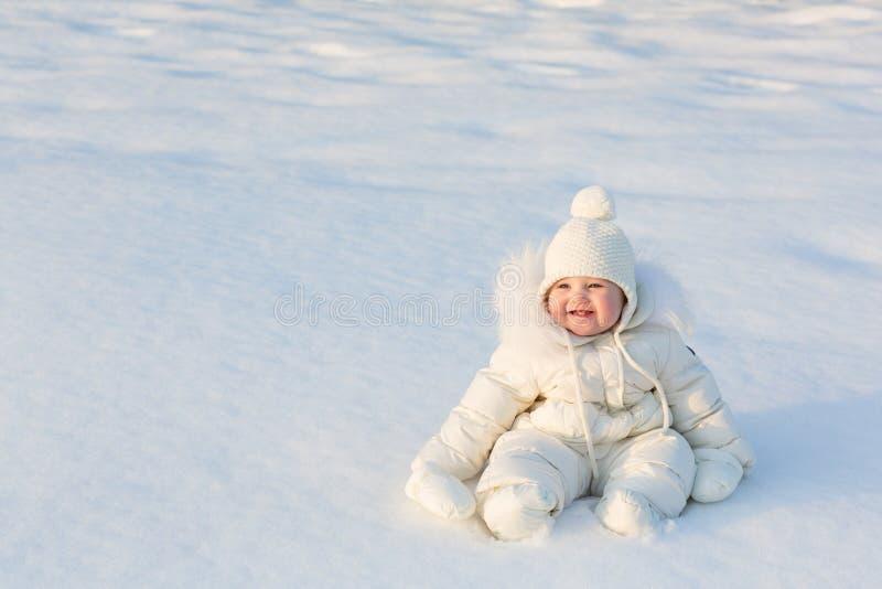 Bello bambino in un vestito bianco della neve che si siede sulla neve fresca fotografia stock