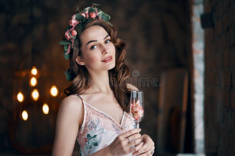 Bello bicchiere di vino della tenuta della donna con i petali rosa fotografia stock