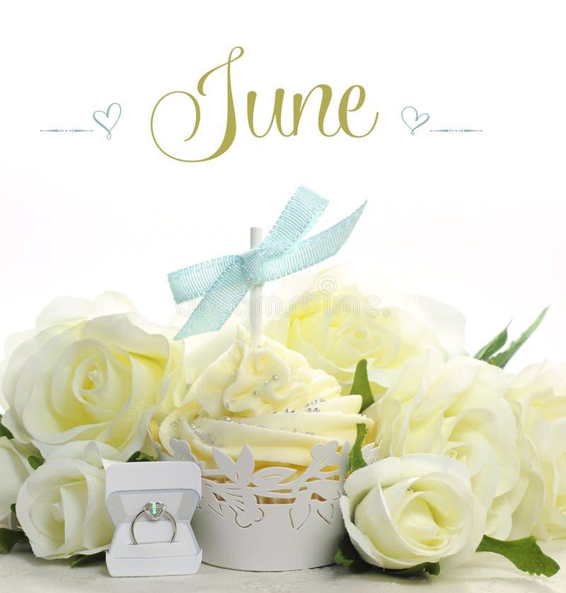 Bello bigné bianco di tema della sposa di giugno con i fiori e le decorazioni stagionali per il mese di giugno immagini stock