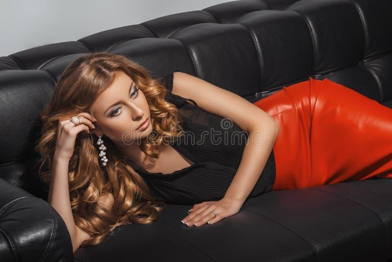 Bello biondo in gonna di cuoio rossa che si trova sul divano di cuoio nero Acconciatura riccia lunga immagini stock libere da diritti