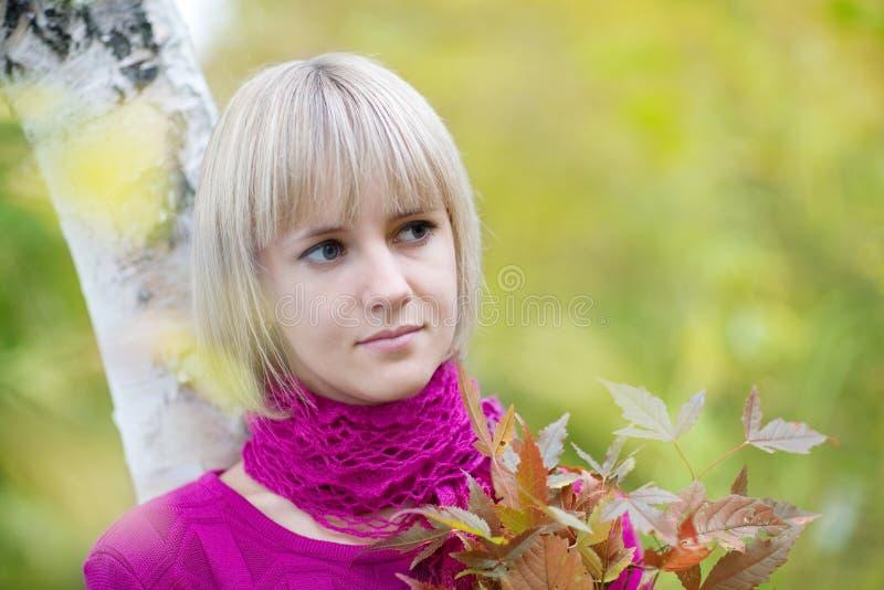 Bello blonde al fogliame di caduta fotografie stock