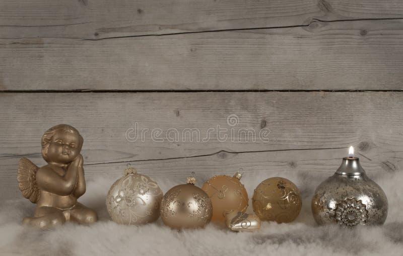 Bello bronzo e bagattelle di natale e candela ed angelo di vetro dorati, sulla pelle di pecora immagine stock