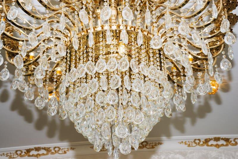 Bello candeliere a cristallo con le lampadine d'ardore che pendono dal soffitto fotografie stock libere da diritti