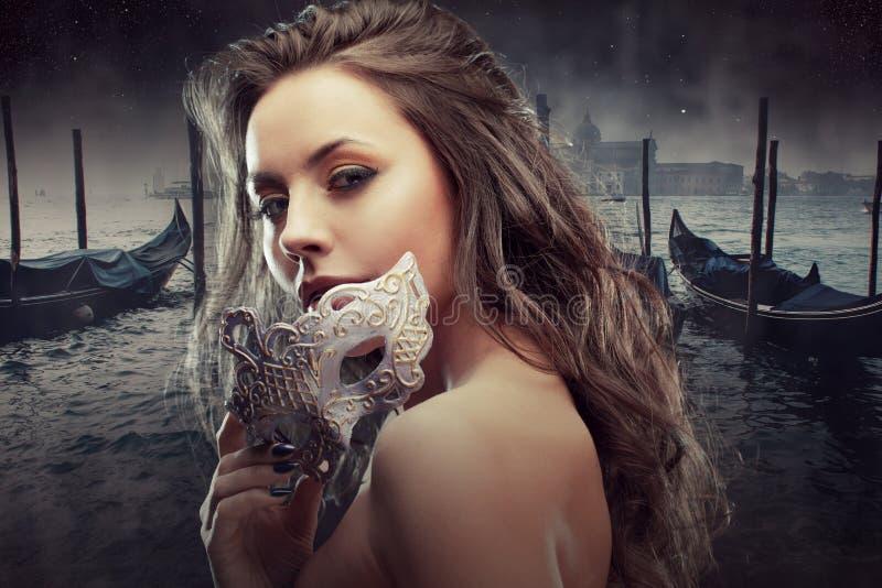 Bello castana con la maschera veneziana Giovane e bella donna sul fondo veneziano di vista, gondole immagine stock
