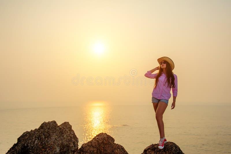 Bello castana con le gambe lunghe in cappello di paglia e breve denim mette sta sulla grande pietra contro il tramonto sopra l'oc fotografie stock libere da diritti