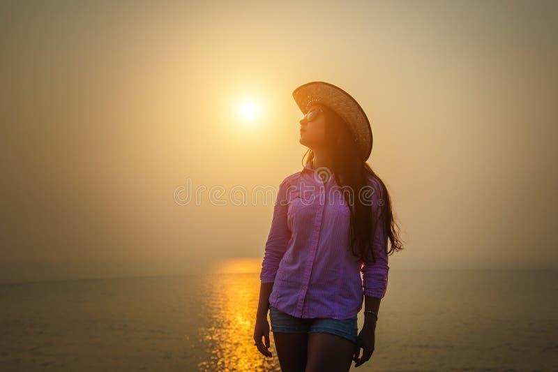 Bello castana dai capelli lunghi in cappello di paglia ed occhiali da sole contro il tramonto sull'oceano La giovane donna ammira immagine stock