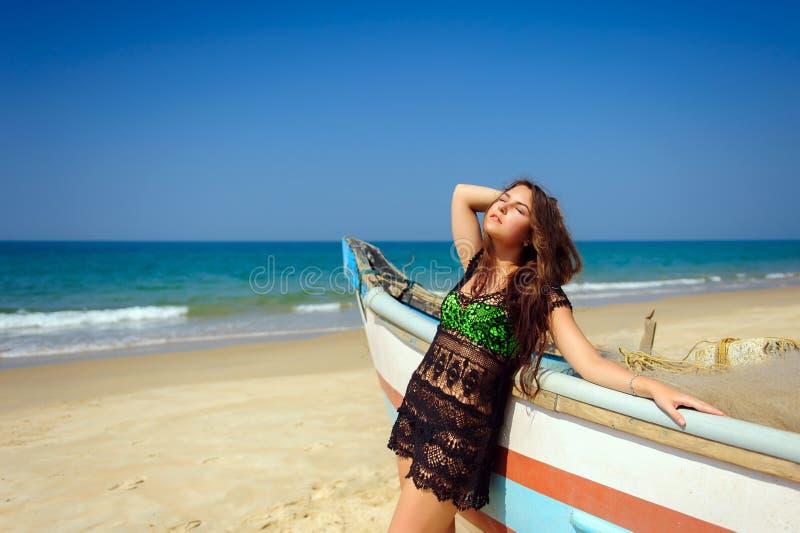 Bello castana dei giovani in vestito dalla spiaggia sul mare blu vicino al peschereccio di legno Rilassamento tropicale di estate immagine stock libera da diritti