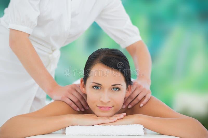 Bello castana godendo di un massaggio della spalla che sorride alla macchina fotografica immagine stock libera da diritti