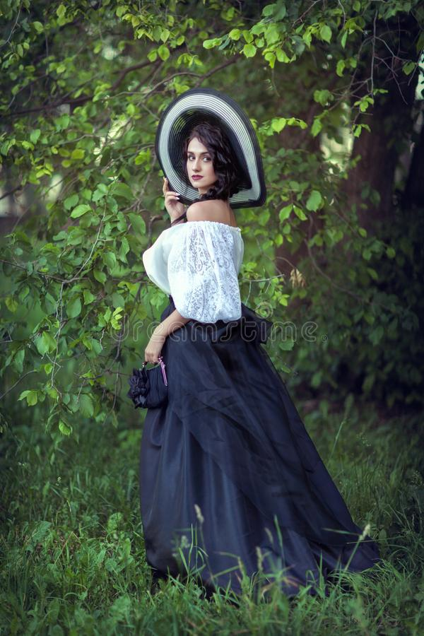 Bello castana in un grande cappello in bianco e nero immagini stock