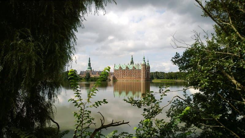 Bello castello di Frederiksborg in Danimarca Nel telaio un lago e un fogliame tranquilli degli alberi e dei cespugli immagini stock