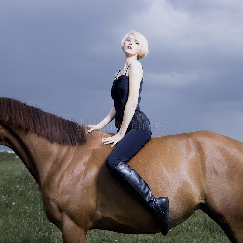 Bello cavaliere biondo della ragazza a cavallo fotografia stock