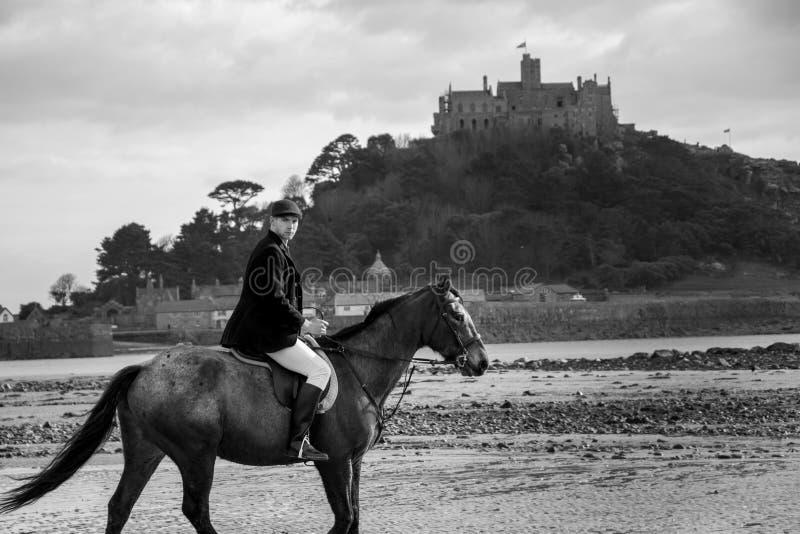 Bello cavallo da equitazione del cavaliere del cavallo maschio sulla spiaggia in abbigliamento tradizionale di guida con il suppo fotografia stock