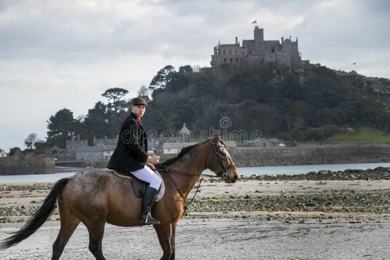 Bello cavallo da equitazione del cavaliere del cavallo maschio sulla spiaggia in abbigliamento tradizionale di guida con il suppo immagine stock