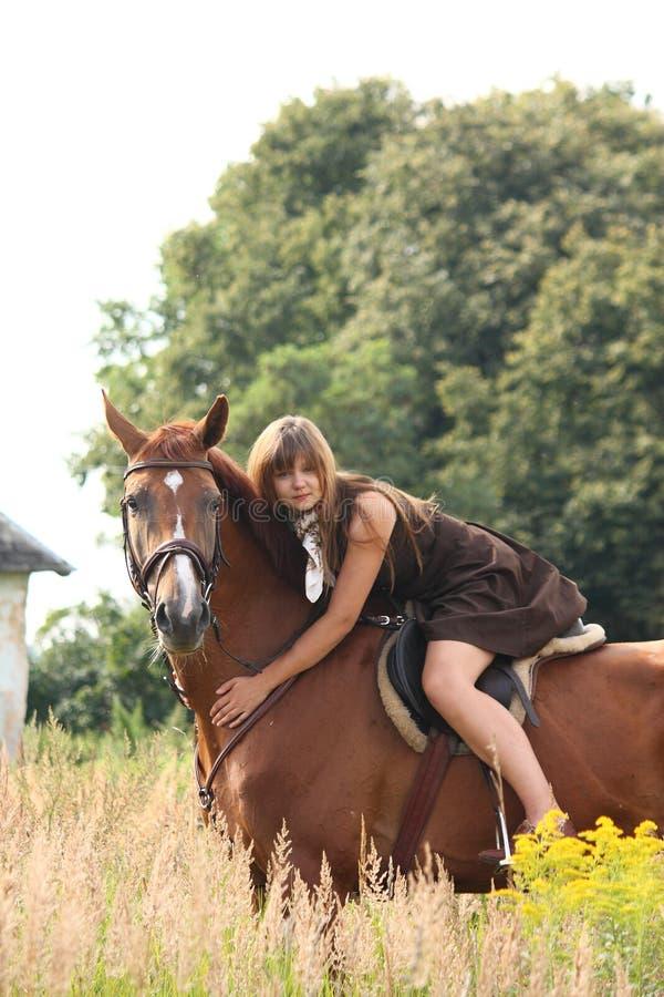 Bello cavallo da equitazione della ragazza dell'adolescente al campo dei fiori fotografia stock