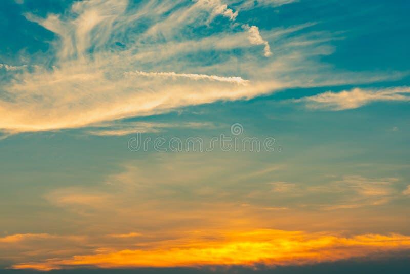 Bello cielo blu e dorato e fondo astratto delle nuvole Nuvole giallo arancione sul cielo di tramonto Fondo caldo del tempo Arte immagini stock libere da diritti
