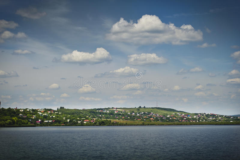 Bello cielo calmante del paesaggio, villaggio, blu del lago immagine stock libera da diritti