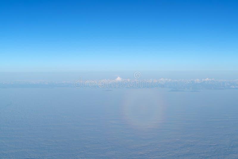 Bello cloudscape con l'alone magico dalla finestra piana immagine stock