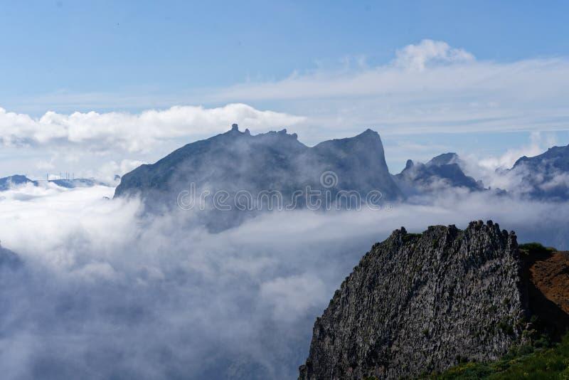Bello colpo dalla cima della montagna sopra le nuvole con una montagna nella distanza fotografia stock