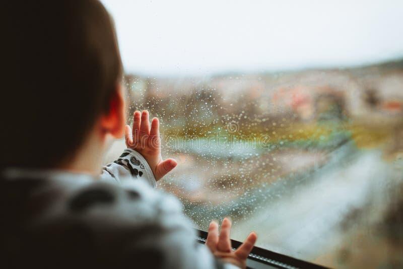 Bello colpo del primo piano di un bambino che guarda attraverso una finestra di vetro con le gocce di pioggia su  immagine stock libera da diritti