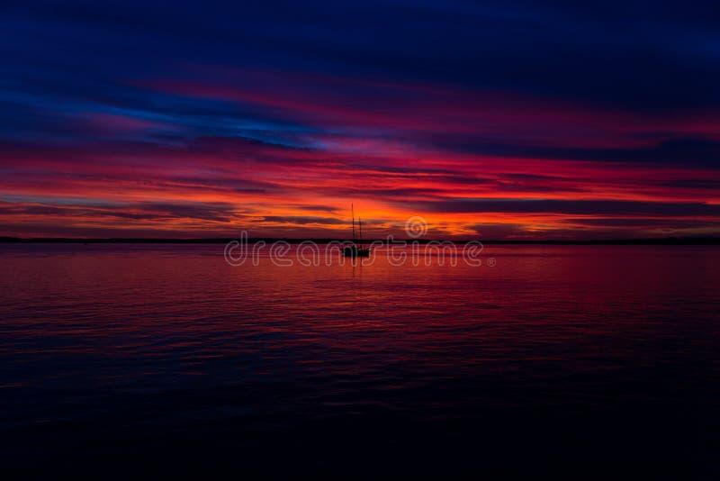 Bello colpo del tramonto alla spiaggia con una barca nel mezzo fotografia stock