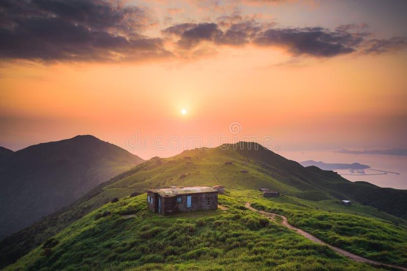 Bello colpo di una casetta costruita su una collina verde pacifica alta su nelle montagne immagine stock