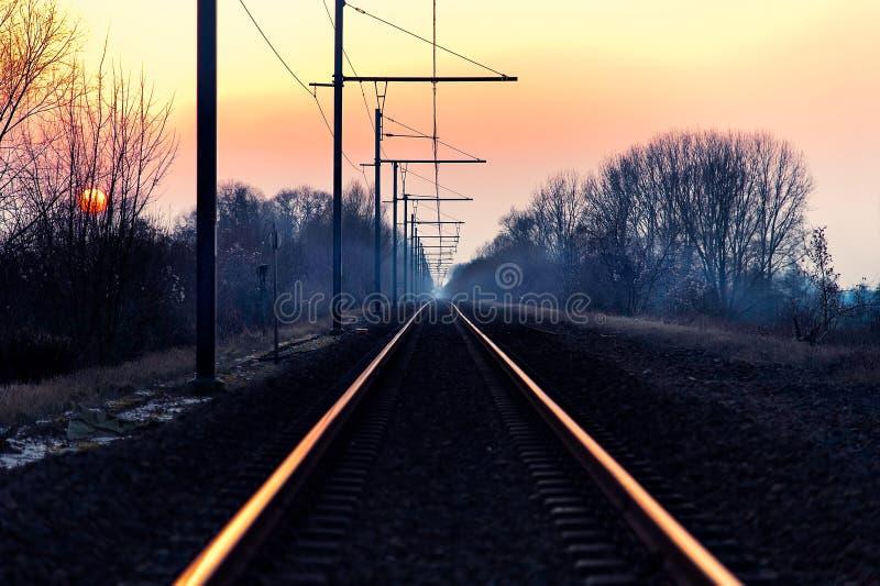 Bello colpo di una ferrovia nella campagna con il cielo rosa stupefacente all'alba fotografia stock