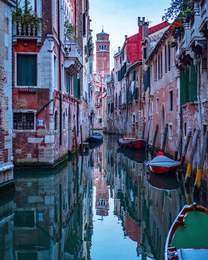 Bello colpo di Venezia con le costruzioni variopinte e le barche riflesse nel canale immagine stock libera da diritti