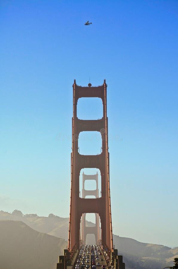 Bello colpo verticale di un ponte occupato con i lotti di traffico e di un aeroplano che vola al di sopra fotografia stock libera da diritti
