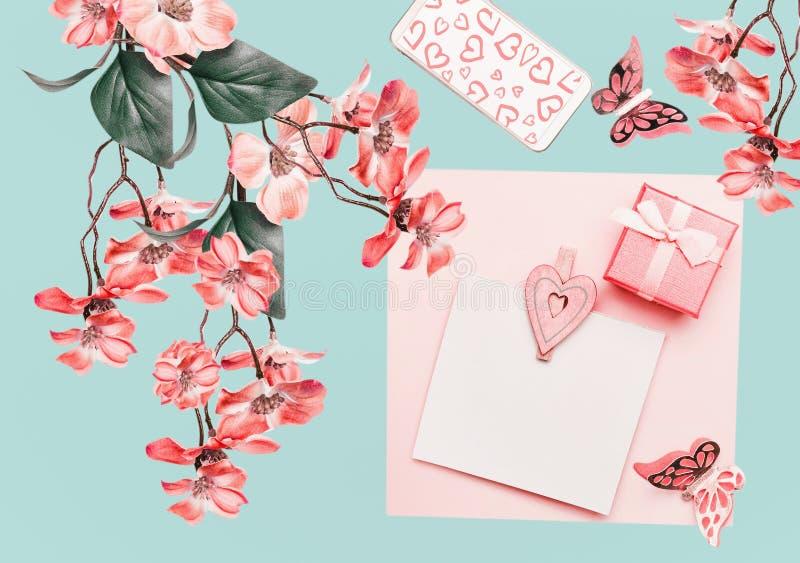 Bello comporre floreale con la cartolina d'auguri, fiori di corallo sboccia ramo d'attaccatura su turchese leggero Disposizione f fotografie stock libere da diritti