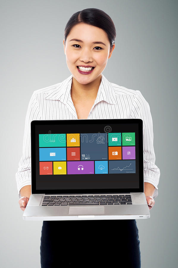 Bello computer portatile sorridente della tenuta della donna fotografia stock libera da diritti