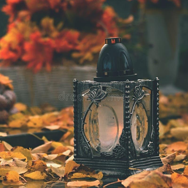 Bello concetto di autunno al cimitero ed al Halloween Candela in una lanterna sulla tomba fondo per Halloween immagini stock libere da diritti