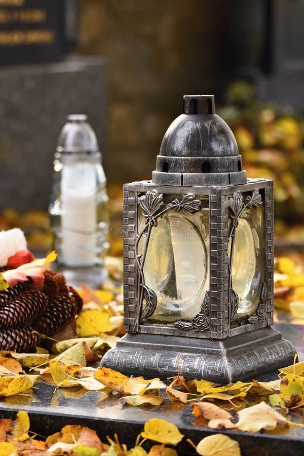 Bello concetto di autunno al cimitero ed al Halloween Candela in una lanterna sulla tomba fondo per Halloween fotografie stock libere da diritti